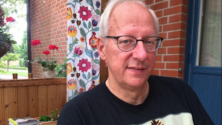En man i kort vitt hår, glasögon och svart tröja.