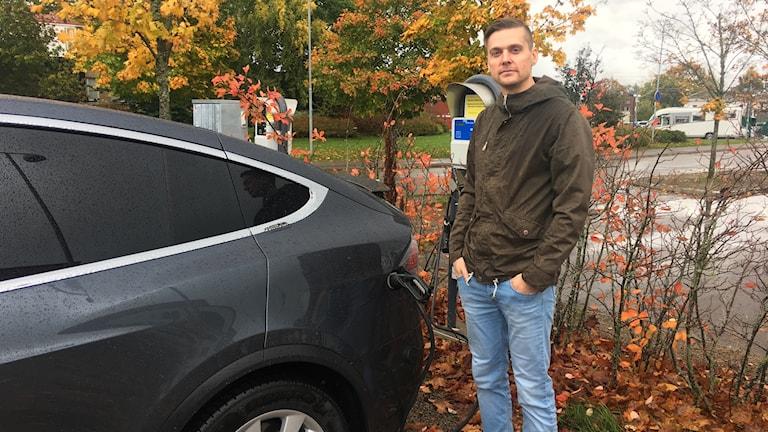Bennie står vid sin elbil. Det är en bil som bara går på el. Bilen är svart med tonade rutor. Bennie har en brun jacka blå, jeans. Han har vattenkammat hår och händerna i byxfickan.