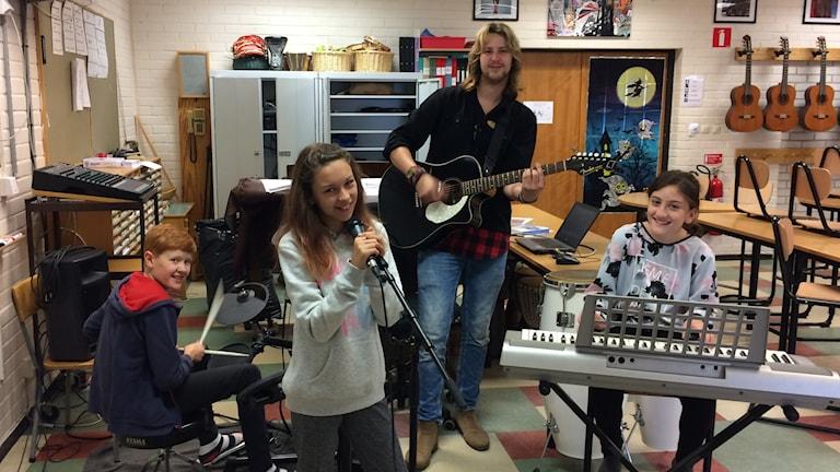Eleverna Anna-Maria Proca, Gustav Johansson och Mariah Alnajjar på grönkulla skolan sjunger skolans låt tillsammans med sin musiklärare Tim Lööv.