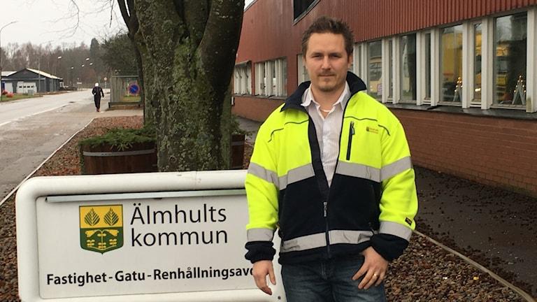 En man i gul reflexjacka står utomhus framför en skylt med texten Älmhults kommun. Fastighet-Gatu-Renhållningsavdelning