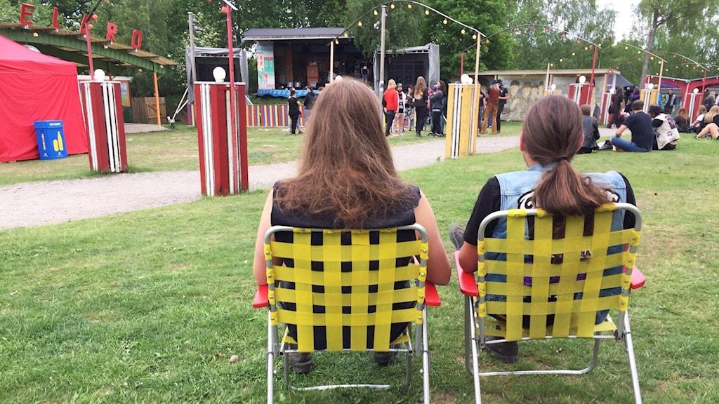 Ryggarna på två personer med långt hår som sitter i två stolar och spanar ut över området.