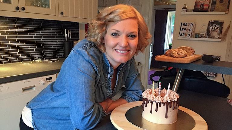 Veronika Dahl står och lutar sig över en tårta