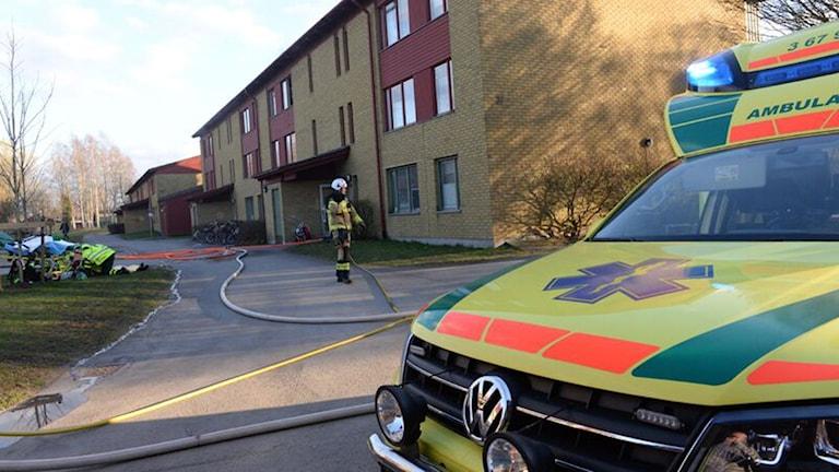 Brandmän utanför ett bostadshus.