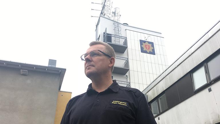 I bild Roger Petersson utanför räddningstjästen. Ibakgrunden syns brandloggan.
