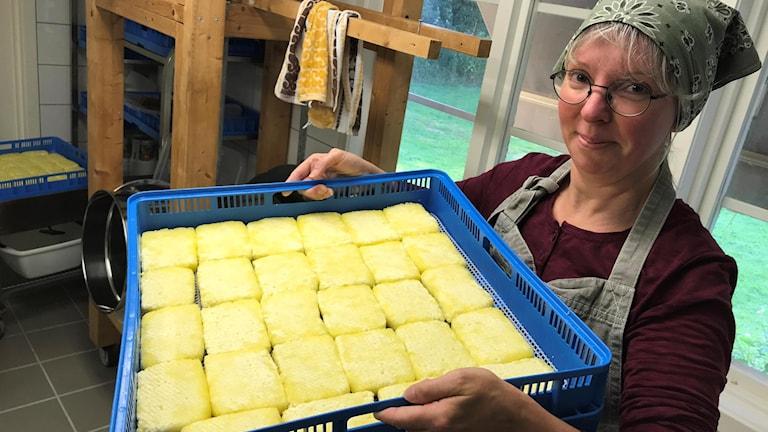 Janni Einarsson från ett gårdsmejeri håller upp en blå back med eldost.