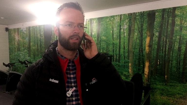 Andreas Rehn, initiativtagare till gymmet i Lidhult, står i gymmet och pratar i mobilen.