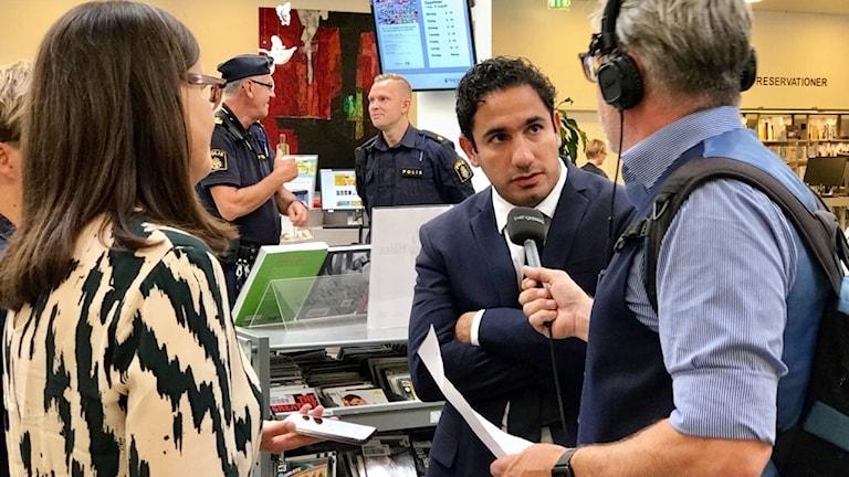Ardalan Shekerabi (S) blir intervjuad av reporter på Sveriges Radio i biblioteket i Växjö.