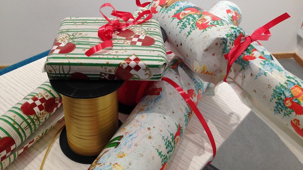 Julklappar på ett bord med paketsnören.