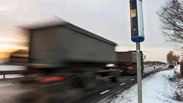 En lastbil kör förbi en fartkamera på en landsväg