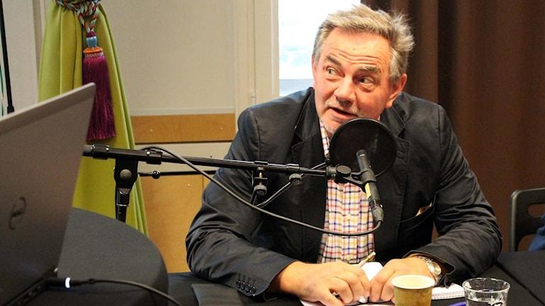 Yngve Filipsson sitter vid ett bord med mikrofon.