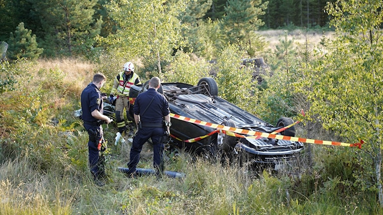En bil ligger upp och ner i terrängen efter olycka. Polis och räddningspersonal står bredvid.