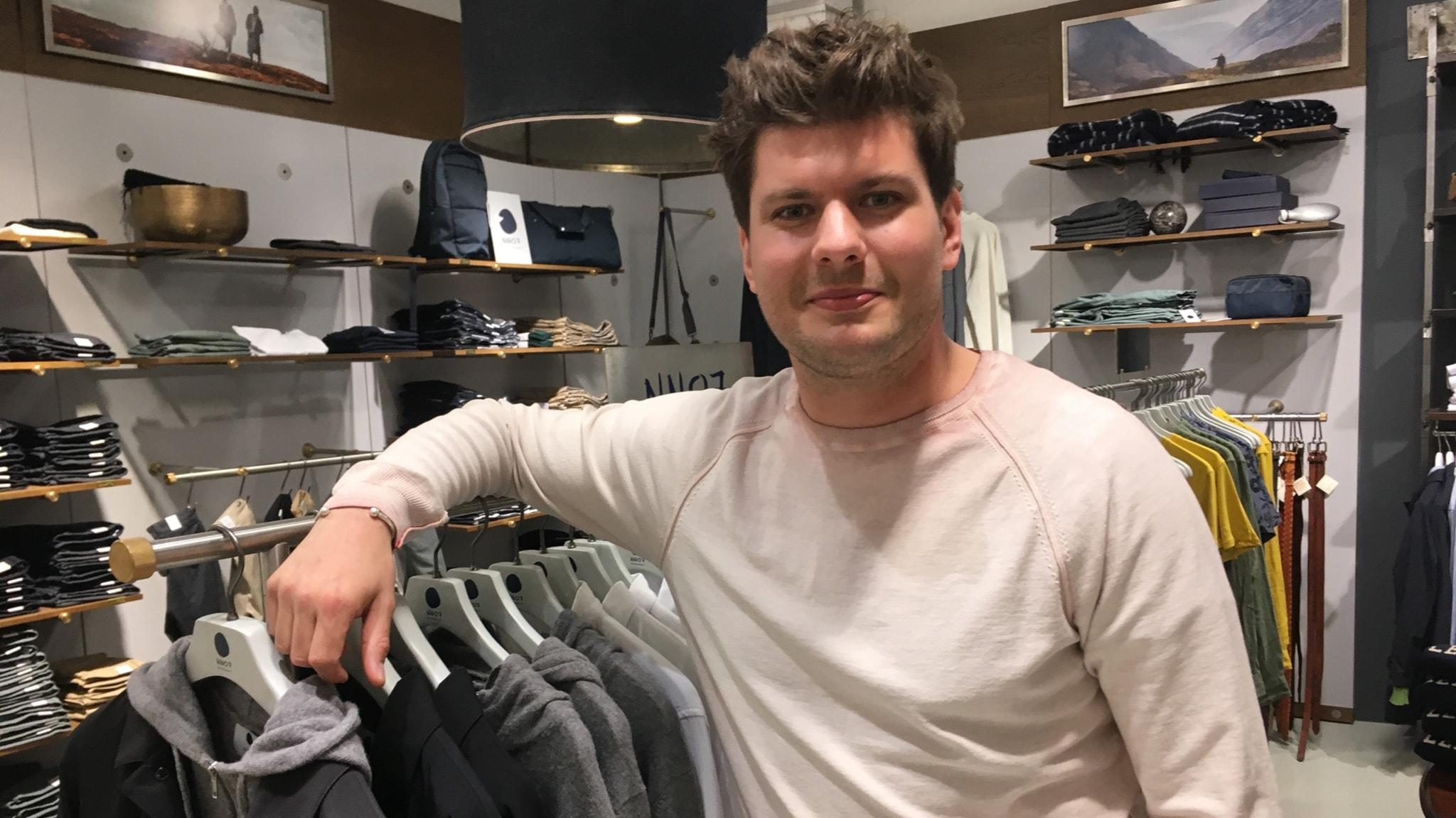 """En man står i en klädbutik och """"hänger"""" över en hängare med tröjor"""