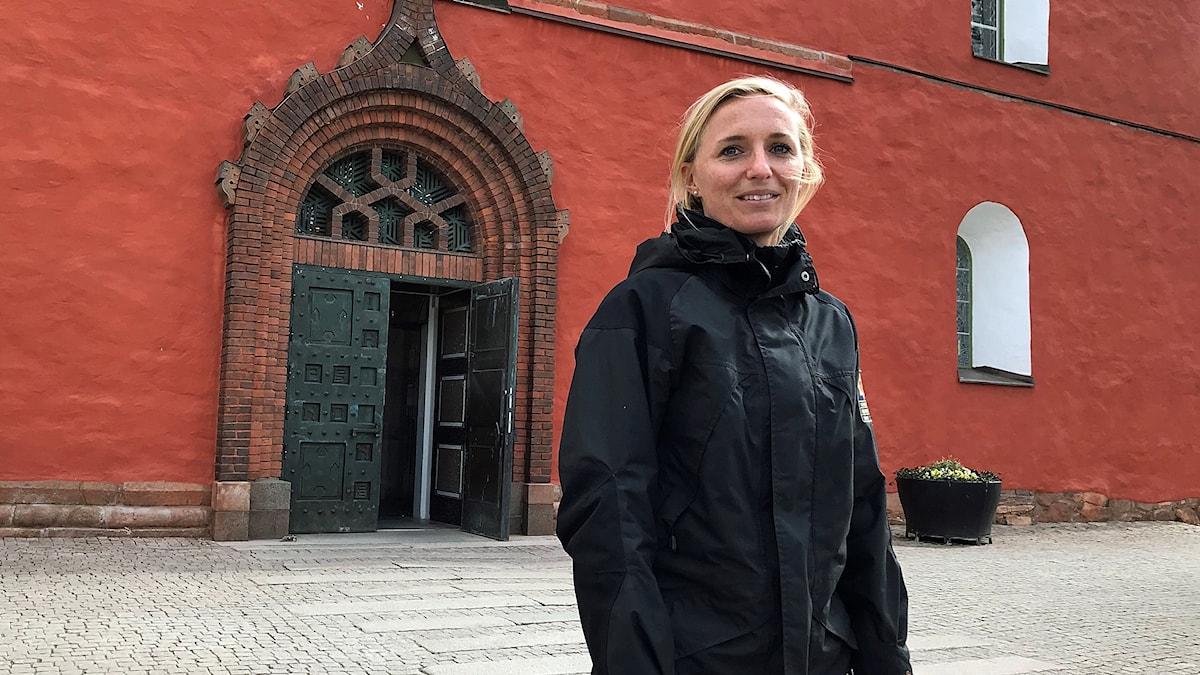 Nellie-Kim Millbourn står framför Växjö domkyrka