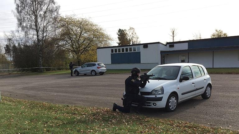 En polis står bakom bil med vapen draget.