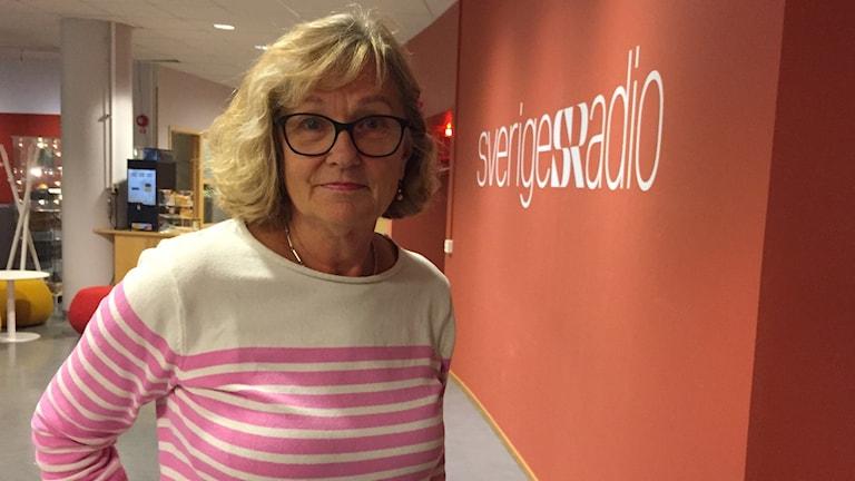 En kvinna i randig tröja, kort blont hår och glasögon står framför en vägg med Sveriges radio-logga.