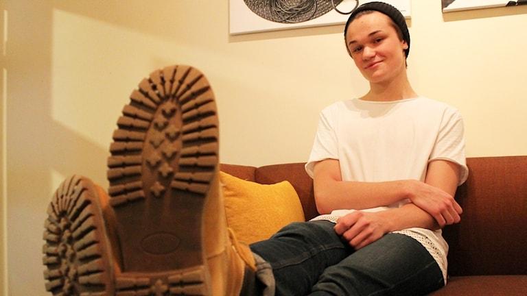 Thomas Sekelius sitter i en soffa med skorna på bordet.