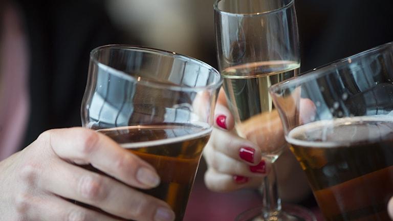 Närbild på tre händer som håller i varsitt glas öl eller mousserande och skålar.