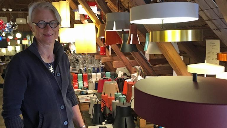En kvinna i kort blont hår och glasögon står bredvid några ovala lampor i olika färger.