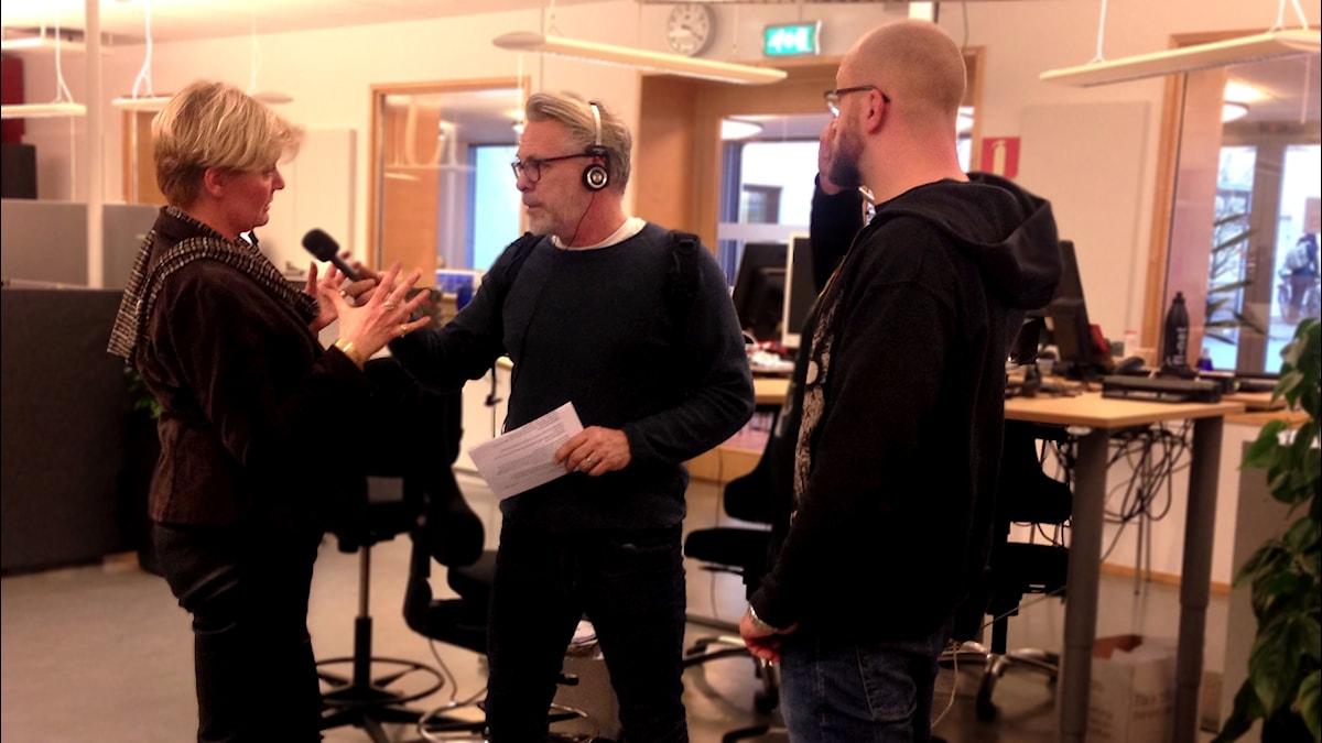 Monica Skagne, kommunchef och Ulf Elm, huvudskyddsombud på fackföreningen Vision intervjuas av Per Brolléus i ett öppet kontorslandskap.