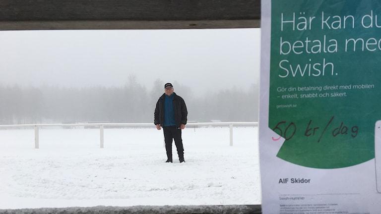 En man står i ett snöigt landskap. I förgrunden sitter en lapp med swish-nummer fasthäftad på ett staket.