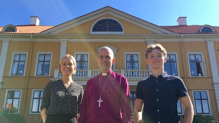 Emma Sjögren, Fredrik Modéus och Zakarias Johansson står framför det stora gula trähuset Östrabo