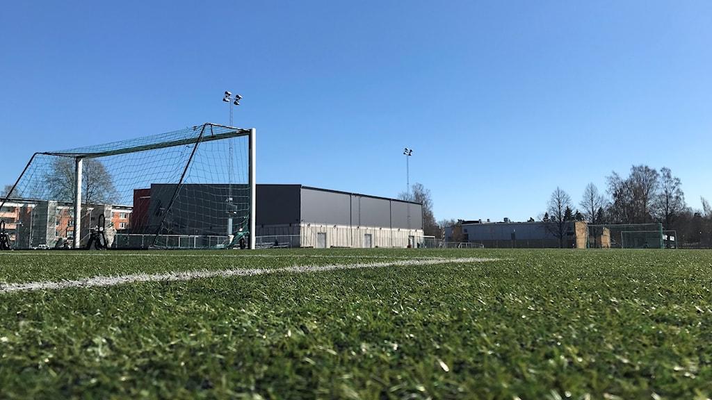 Ett fotbollsmål på en konstgräsplan i strålande solsken.