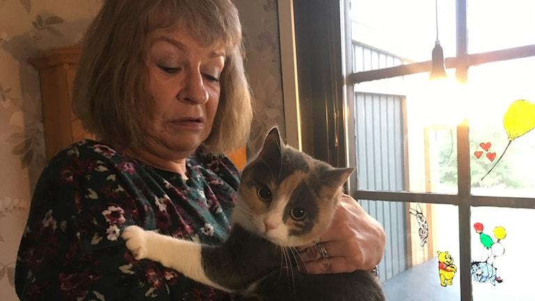 En kvinna står inomhus vid ett fönster och håller i en katt