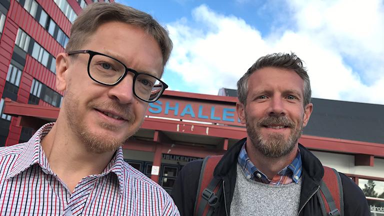 Daniel Westergren och Joacim Martinsson står utanför Tipshallen i Växjö och ler mot kameran med en blå himmel med små vita moln.