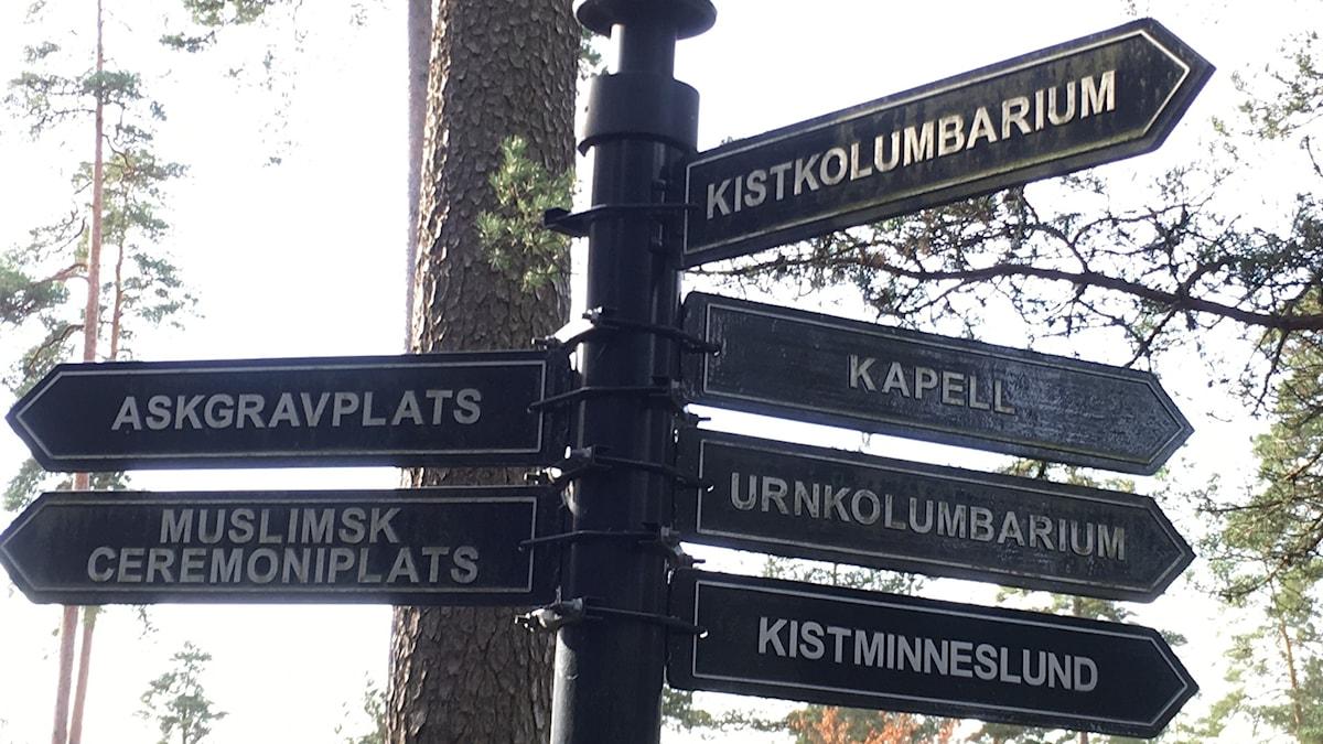 En stolpe med många skyltar till olika delar av kyrkogården; Kapell, Askgravplats, Muslim Ceremoniplats