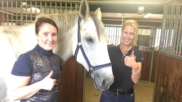 Linn Björkman och Therese Göransson står i stallet tillsammans med en vit häst.
