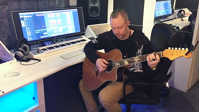 Kim Lindsten sitter med en gitarr i en studio.