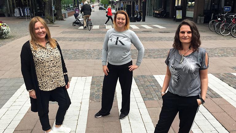 Tre kvinnor står på ett övergångsställe
