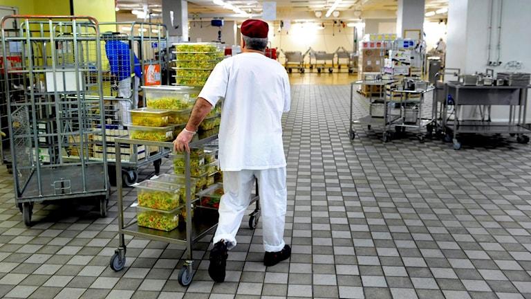 En man går i väg med en matvagn inne i en sjukhusmatsal.