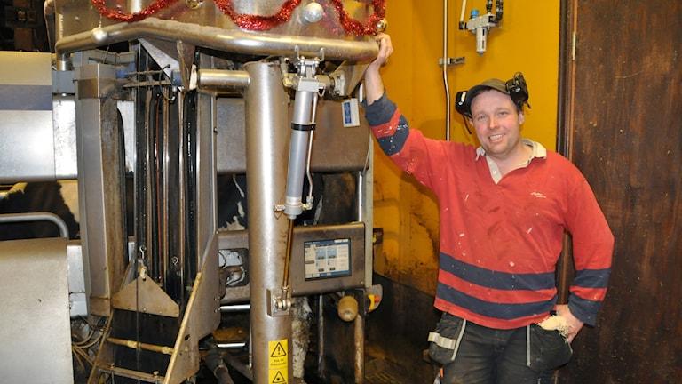 Mjölkbonden Stefan Andersson står vid en mjölkmaskin.