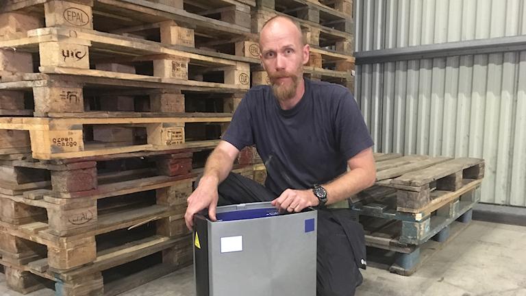 Magnus Ekeroth sitter framför en hög med lastpallar och visar upp en av de digitala råttfällorna som ökat i användning de senaste åren.