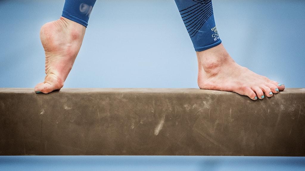 Ett par ben och fötter går på en gymnastikbom.