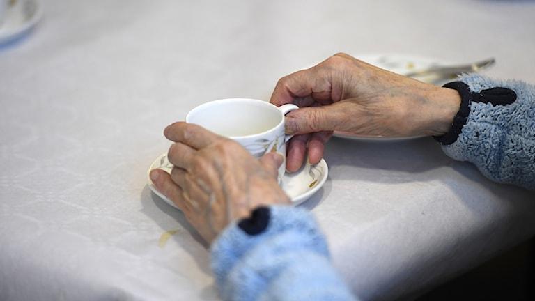 Händer på en äldre person som håller i en kaffekopp.