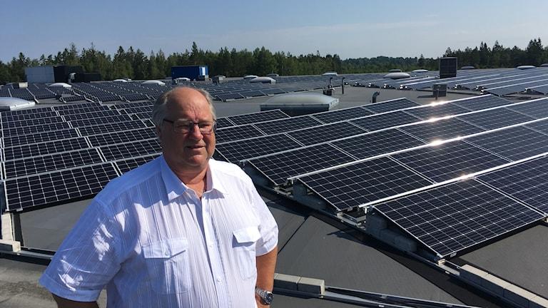 Jan Bladh står på taket på företaget Amokabel framför en mängd solceller.