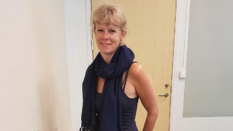 En kvinna med uppsatt blont hår, blått linne och blå sjal.