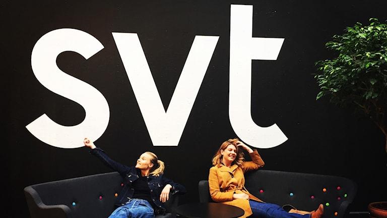 """Två tjejer sitter i en soffa och ser glada ut. Bakom på väggen står det """"svt"""" med stora vita bokstäver."""