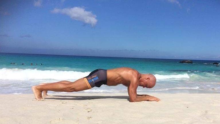 Mikael Bergqvist i plankan på en strand.