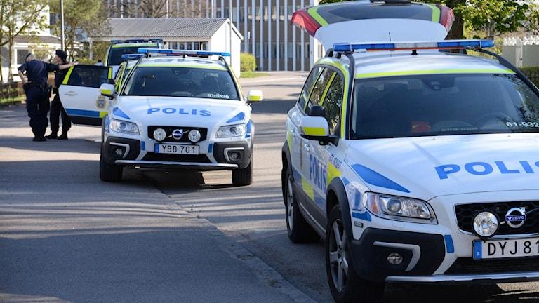 Flera polisbilar på en gata.