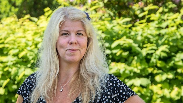 Anna Tornehagen som tävlar i P4 Nästa Kronoberg står framför en grönskande buske.