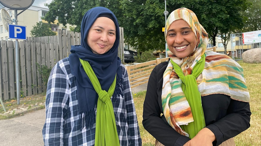 Två kvinnor står i ett bostadsområde.