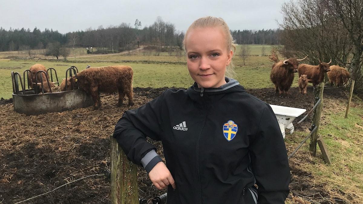 Maja Nyberg från Fathult i Lidhult hemma på gården med kor i bakgrunden.