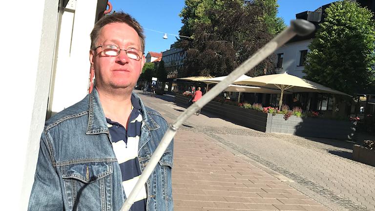 Janne Andersson står med en blindkäpp i luften längs med Storgatan i Växjö.