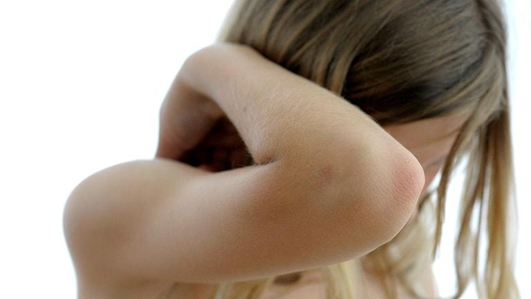 Armbågen på en flicka som håller upp armen som skydd för ansiktet
