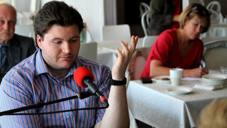 Leon Jensen, Sverigedemokraterna, sitter vid en mikrofon.