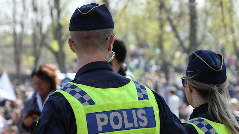 En kvinnlig och manlig polis står med ryggen mot en park i sina uniformer.