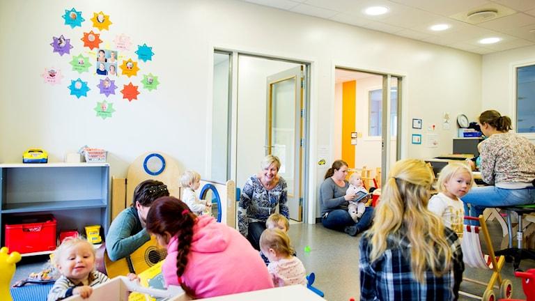 Ett rum med många barn och 6 vuxna som leker på golvet med barnen. Färgglada bilder på väggarna.